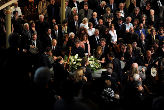 Banjo players tip their instruments to Earl's casket in the Ryman Auditorium at the conclusion of Earl Scruggs' memorial service, April 1, 2012. Photo by CBS News.